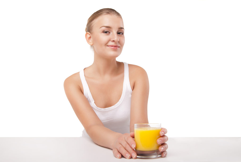 Billede af kvinde der drikker et glas appelsin juice.